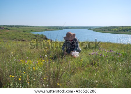 Woman In a straw hat, gathers herbs in the prairies, desert next to a large river. Wonderful sunny day. Azov steppes, Ukraine.