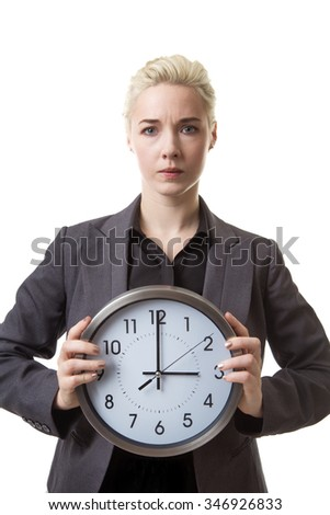 Woman in a suit holding a large clock infront of her with both hands