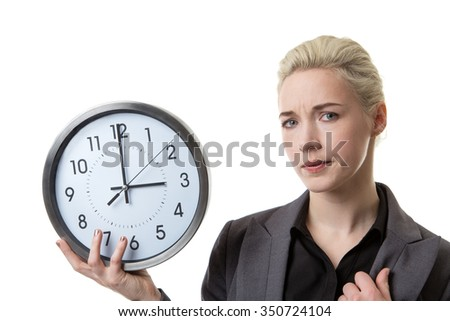 Woman in a suit holding a large clock looking worried