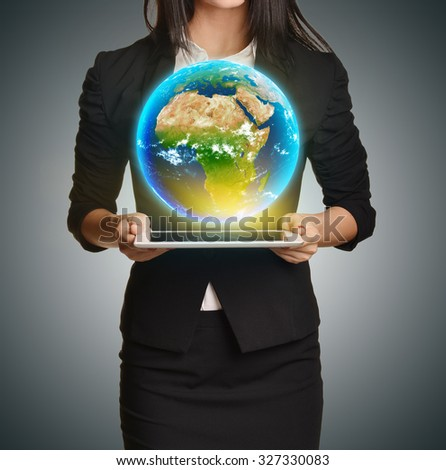 Woman in a suit holding tablet palms and Earth upon him. Elements of this image are furnished by NASA