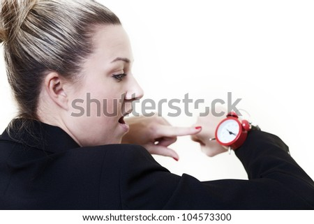 woman in a suit looking at a wrist watch made to look like a traditional alarm clock - stock photo