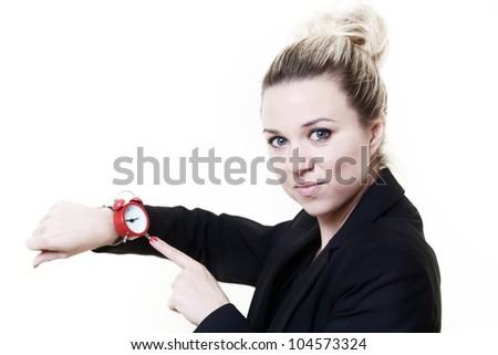 woman in a suit looking at a wrist watch made to look like a traditional alarm clock