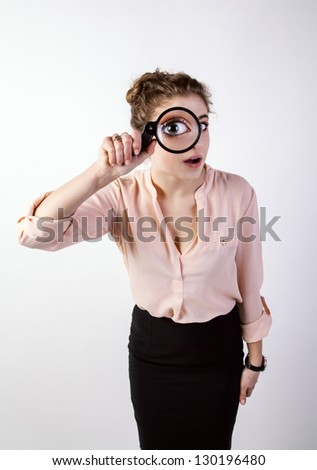 woman in a suit looking through a magnifying glass