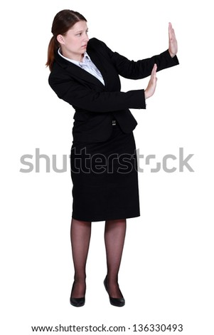 woman in a suit trying to protect herself with her hands