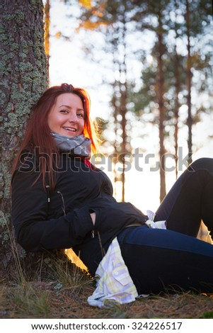 Woman in a sunset lights in autumn forest