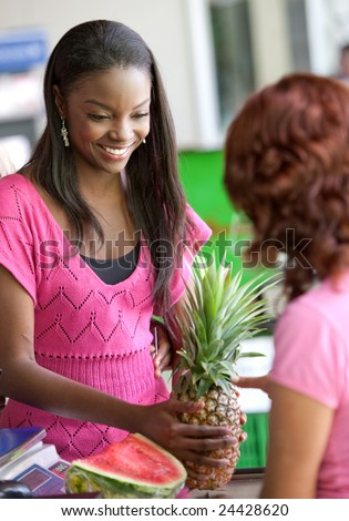 Woman in a supermarket doing shopping paying at the till - stock photo