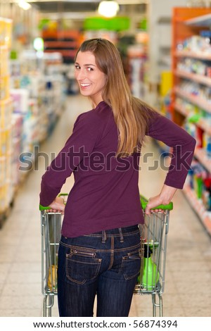 Woman in a supermarket running trough the aisle with a shopping cart