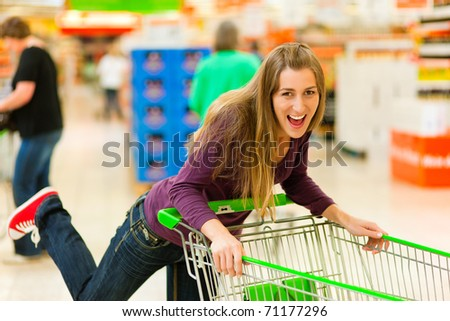 Woman in a supermarket running trough the aisle with a shopping cart and having fun