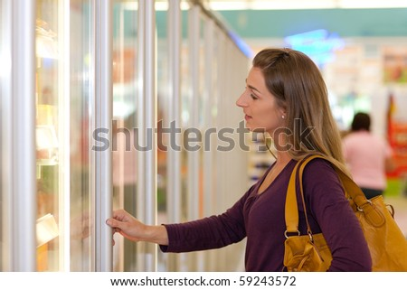 Woman in a supermarket standing in front of the freezer looking for her favorite frozen food