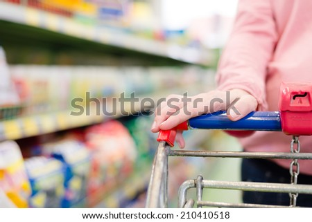 woman in a supermarket trolley carries, closeup on hand