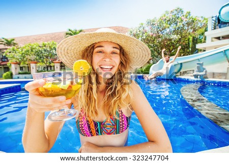 woman in a swimming pool of waterpark holding cocktail and man sliding from the water slide  - stock photo
