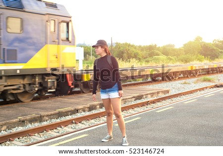 woman in a train station, waiting for her train