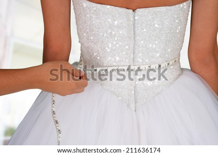 Woman in a wedding dress getting measured  - stock photo