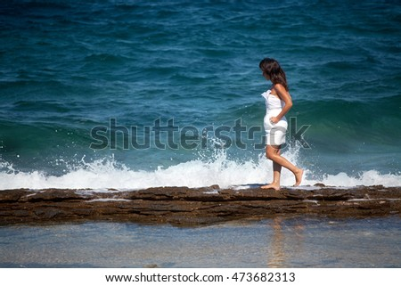 Woman in a white dress walks on the rocky beach