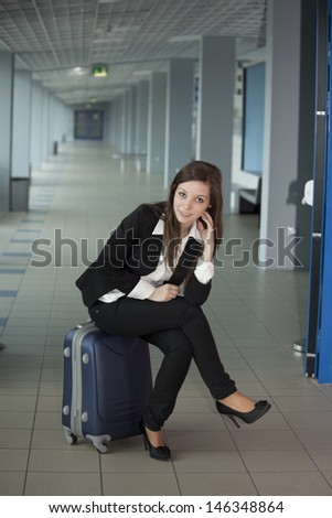 Woman in airport standing on her luggage - stock photo