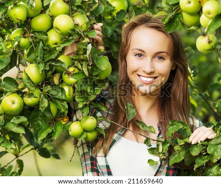 Woman in an apple tree garden during the harvest season. Young smiling beautiful woman is standing among the apple trees with ripe organic apples on it. Healthy country lifestyle concept. - stock photo