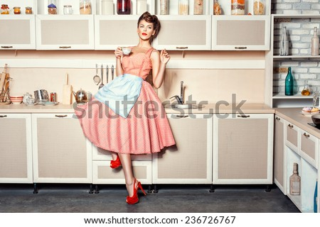 Woman in an apron in the kitchen drinking from a cup and waving.