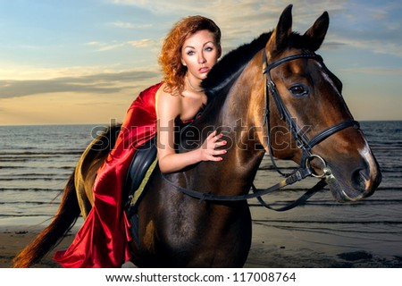 woman in an elegant red dress with a horse on the beach