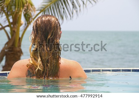 Woman in an infinity pool looks out at the ocean