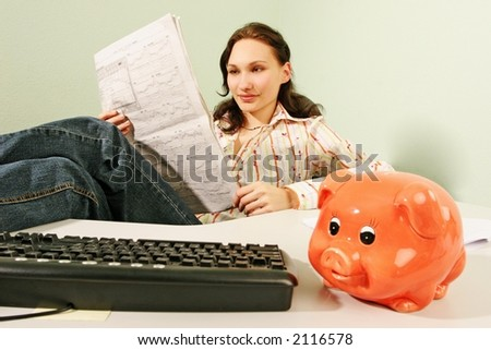 woman in an office reading business statistics of a stock market -with a piggy bank in a foreground