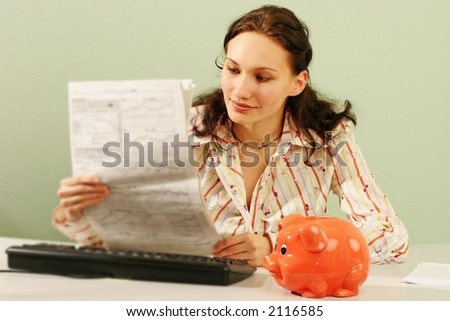 woman in an office reading business statistics of a stock market -with a piggy bank on a desk