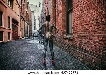 Woman in an urban alley blended into the scene with body paint / urban camouflage