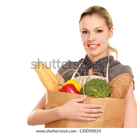 Woman in apron holding grocery bag - stock photo