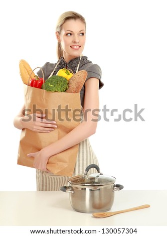 Woman in apron holding grocery bag , isolated on white background - stock photo