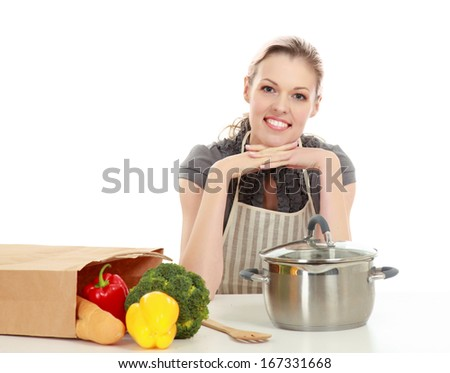 Woman in apron sitting on the desk with grocery bag , isolated on white background - stock photo