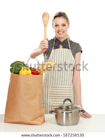 Woman in apron standing near desk with grocery bag , isolated on white background - stock photo