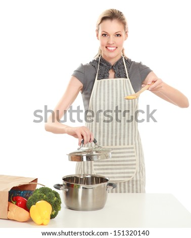 Woman in apron standing near table with grocery bag , isolated on white background - stock photo