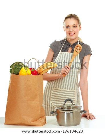 Woman in apron standing near table with grocery bag , isolated on white background
