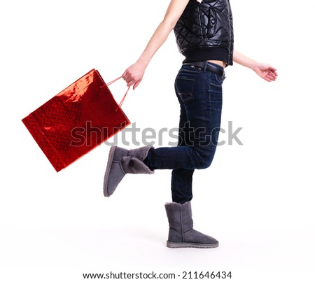 Woman in autumn boots and blue jeans with red shopping bag standing -  isolated on white. - stock photo