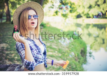 Woman in Autumn Forest sitting on the banch , blowing soap bubbles