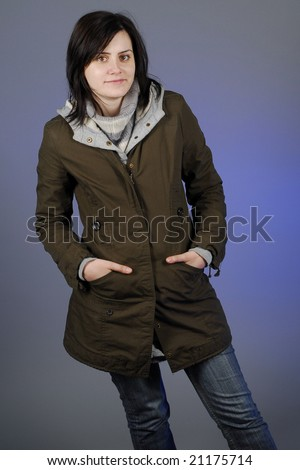 Woman in autumn/winter clothes posing in studio - stock photo