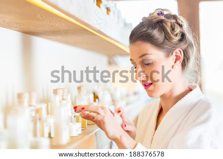 Woman in bath robe choosing face care products in wellness spa  - stock photo