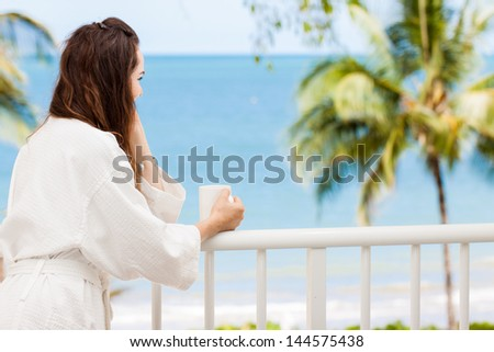 Woman in bath robe looking at beautiful ocean view  from a tropical balcony with morning coffee. - stock photo