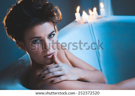 Woman in bath tub with candles - stock photo