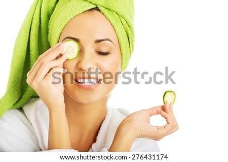 Woman in bathrobe applying cucumber on eyes. - stock photo