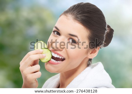 Woman in bathrobe eating piece of cucumber. - stock photo