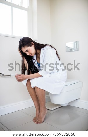 Woman in bathrobe looking at her pregnant test in toilet - stock photo