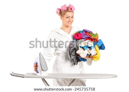 Woman in bathrobe preparing clothes for ironing isolated against white background - stock photo