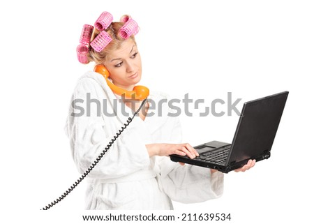 Woman in bathrobe talking on phone and working on laptop isolated on white background - stock photo
