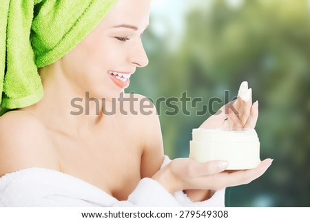 Woman in bathrobe with body lotion. - stock photo