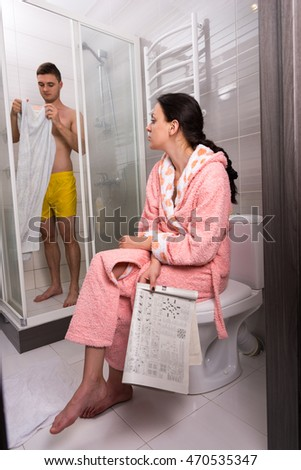 Woman in bathrobe with newspaper sitting on a toilet and waiting for her boyfriend while he toweling  in shower-cabin with transparent glass doors in the bathroom
