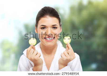 Woman in bathrobe with piece of cucumber. - stock photo