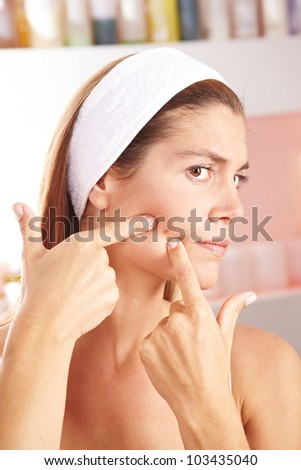 Woman in bathroom squeezing pimple on her cheek - stock photo