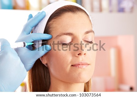 Woman in beauty clinic getting botox injection to remove eye wrinkles