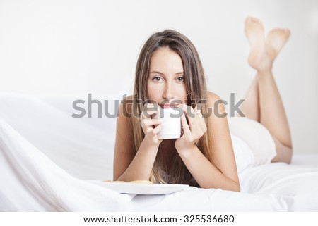 Woman in bed drinking coffee. Woman enjoying coffee in the bed in the morning
