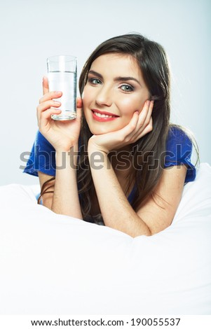 Woman in bed hold water glass. Smiling girl.